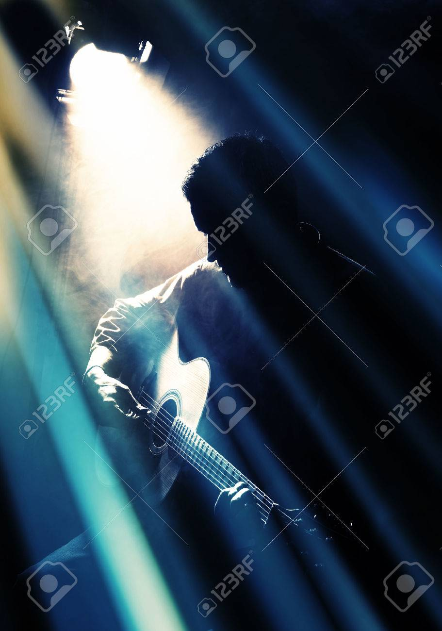 Guitarist playing acoustic guitar. Unplugged performance in the dark. Stock Photo - 34980661