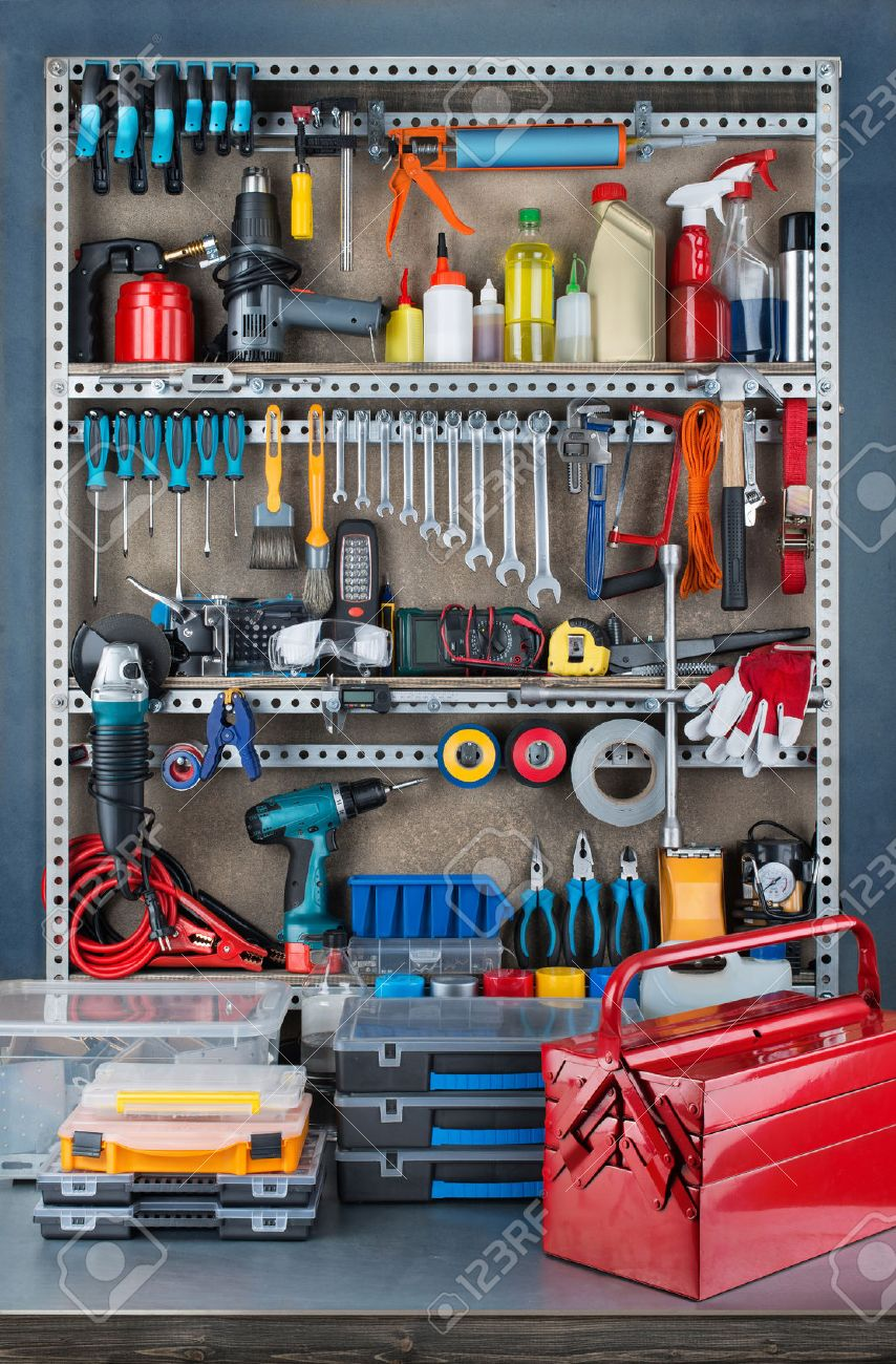 Garage tool rack with various tools and repair supplies on board and shelves. Stock Photo - 42120749