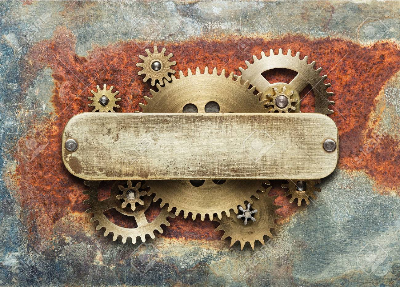 Clockwork mechanism on rusty background made of metal gears and brass plate. Stock Photo - 48054376