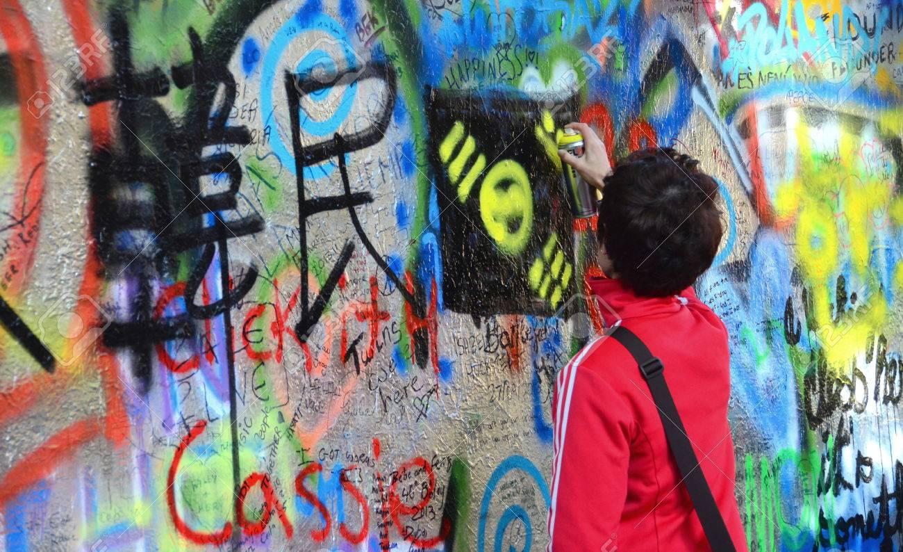 Prague czech republic oct 13 unidentified person adding grafitti to the john lennon