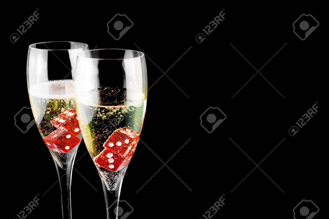 red dice in a champagne flute on black background - 11781951