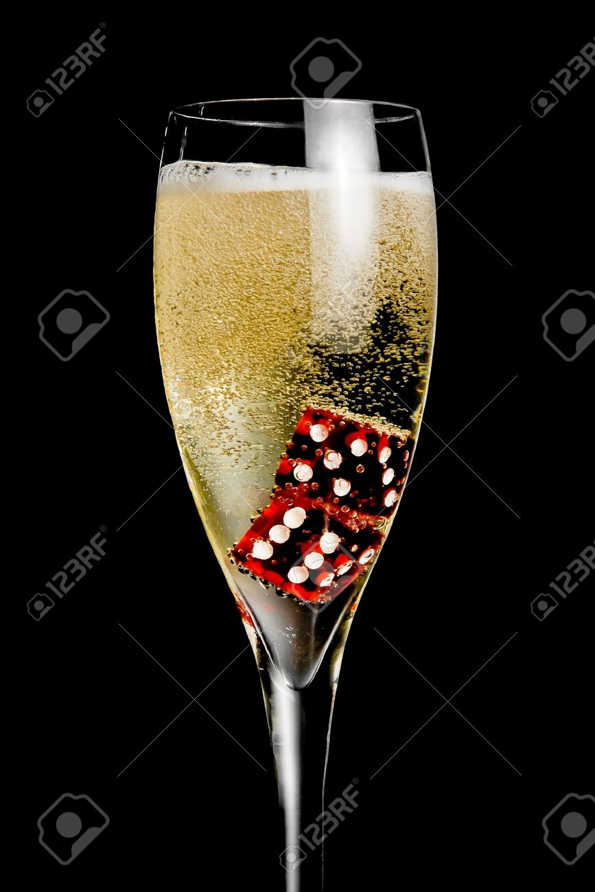 champagne flute with golden bubbles and red dice on black background - 17304496