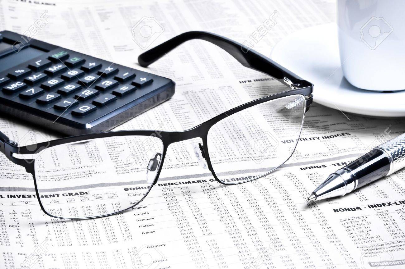 detail of a pen and glasses near a calculator with cup of coffee on financial newspaper - 22668222