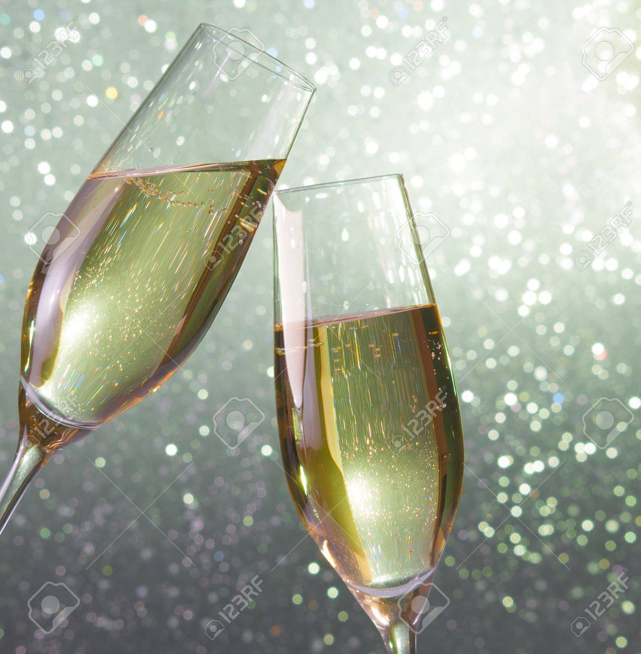 champagne flutes make cheers on silver light bokeh background stock