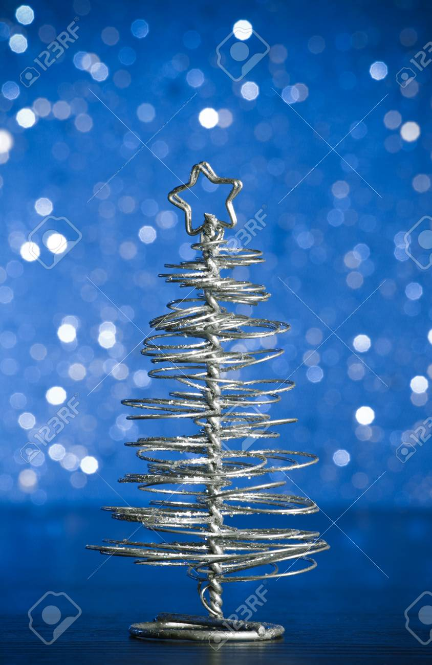 Close Up Of Metallic Modern Christmas Tree On Wood Table On Blue Stock Photo Picture And Royalty Free Image Image 24431710
