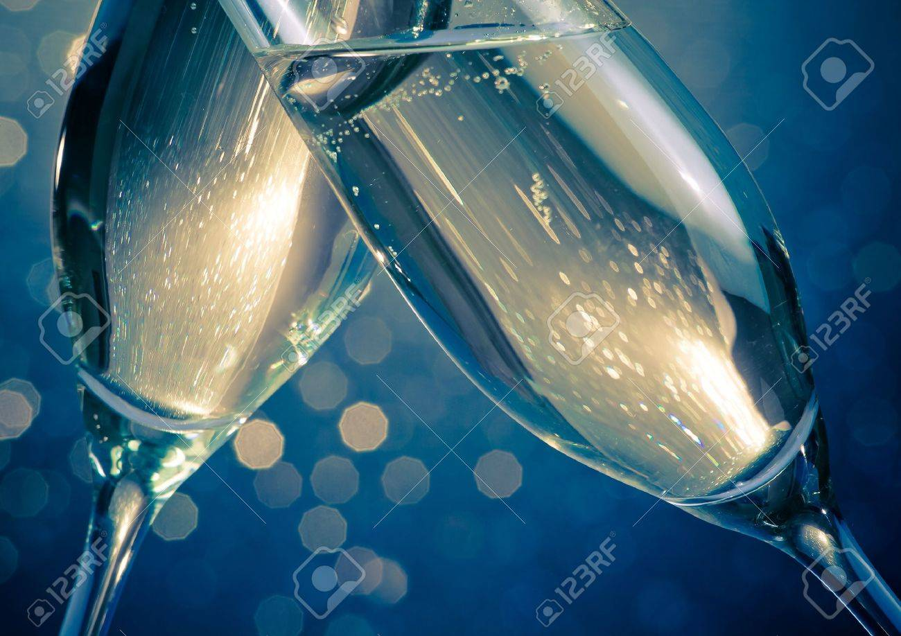 detail of champagne flutes with golden bubbles make cheers on blue light bokeh background with space for text - 24842434