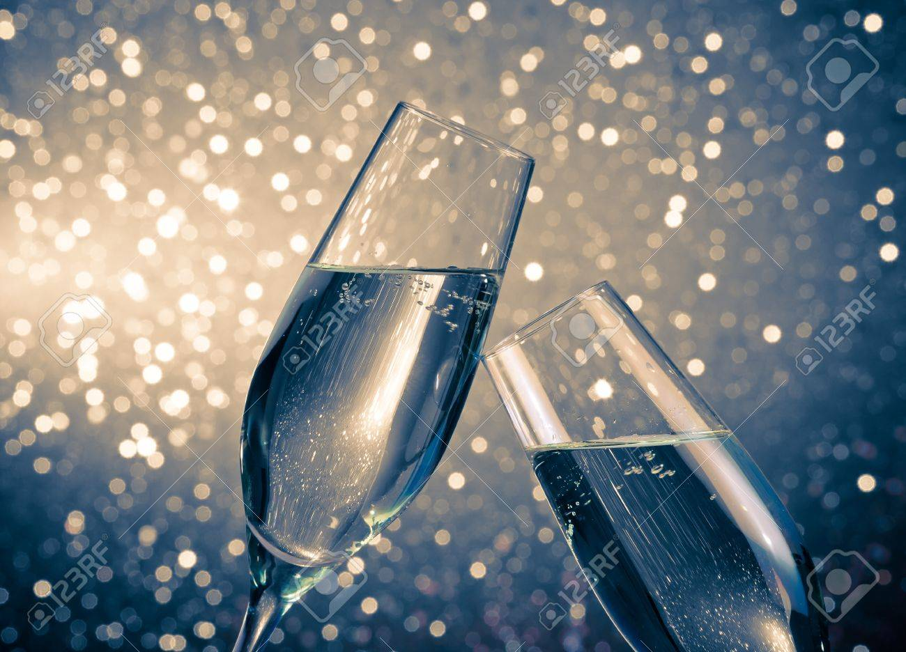 a pair of champagne flutes with golden bubbles make cheers on blue light bokeh background with space for text - 24842475
