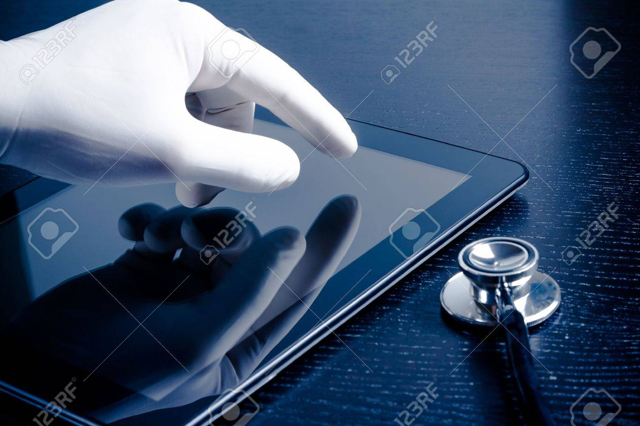 hand in medical glove touching modern digital tablet pc near stethoscope on black wood table. Concept of medical or research theme - 27569991