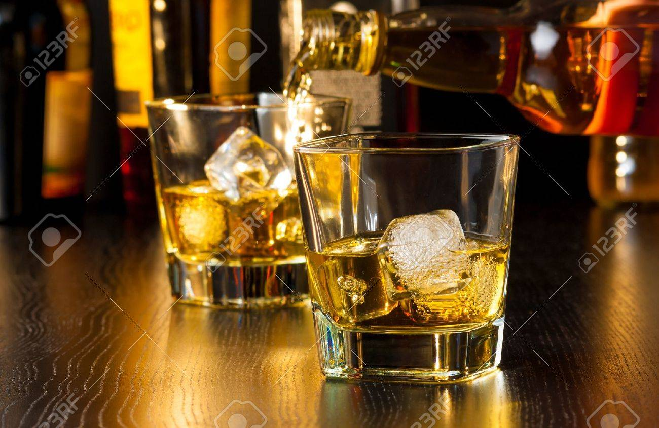barman pouring whiskey behind whiskey glass on wood table - 28756581