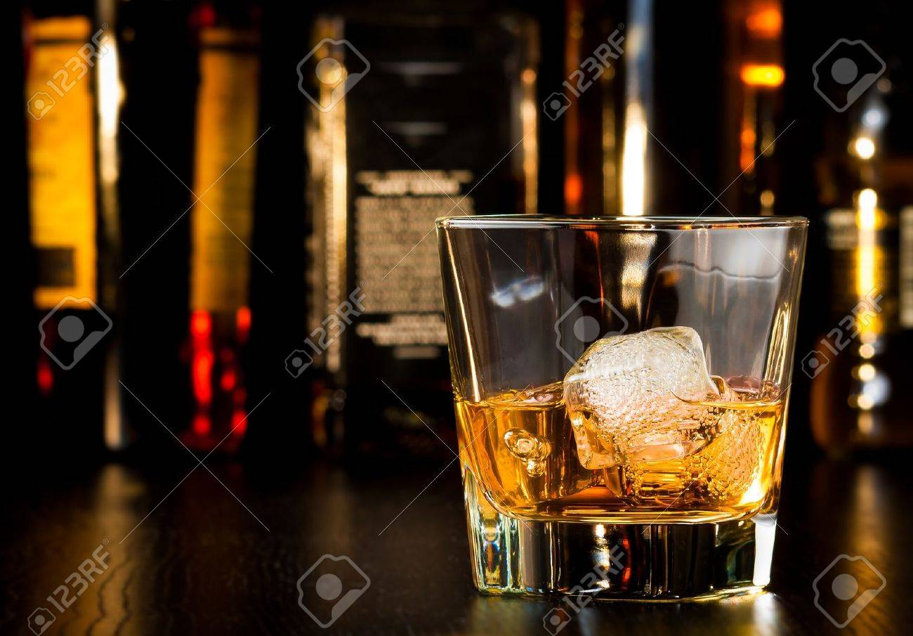 whiskey glass with ice in front of bottles on wood table - 28755714