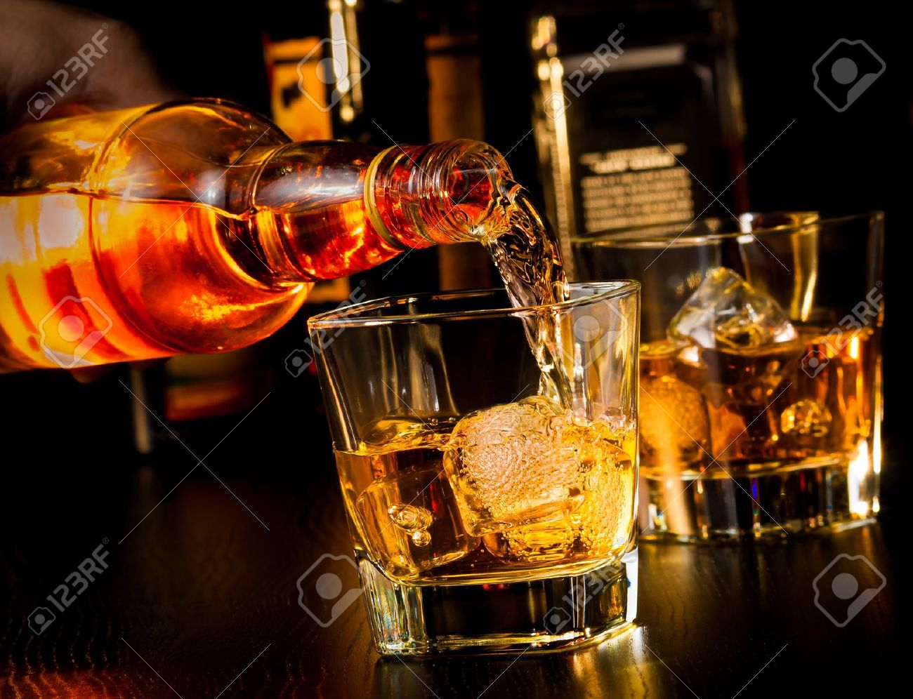 barman pouring whiskey in front of whiskey glass and bottles on wood table - 28755716