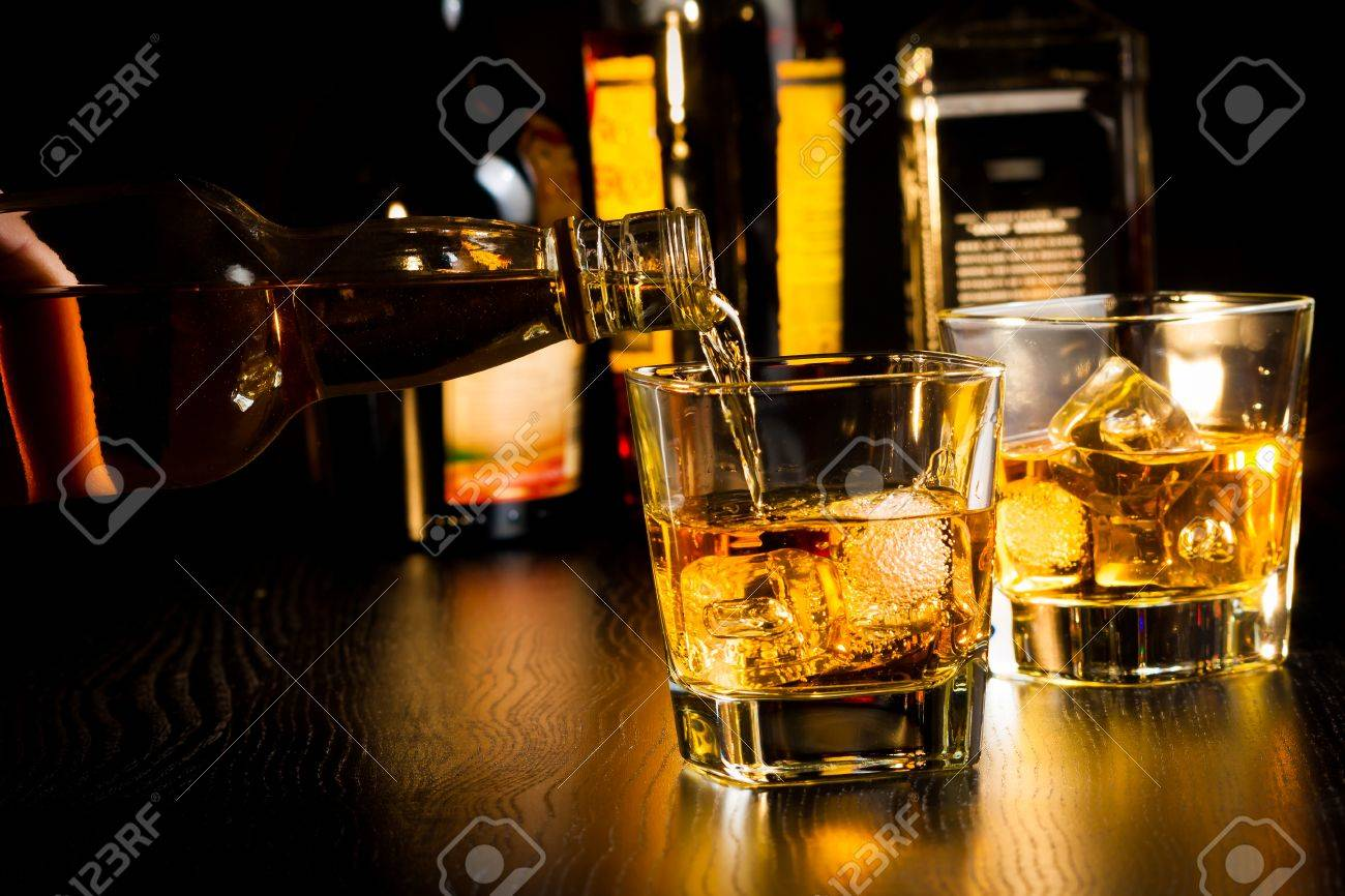 barman pouring whiskey in front of bottles on wood table, focus on top of bottle - 28754359