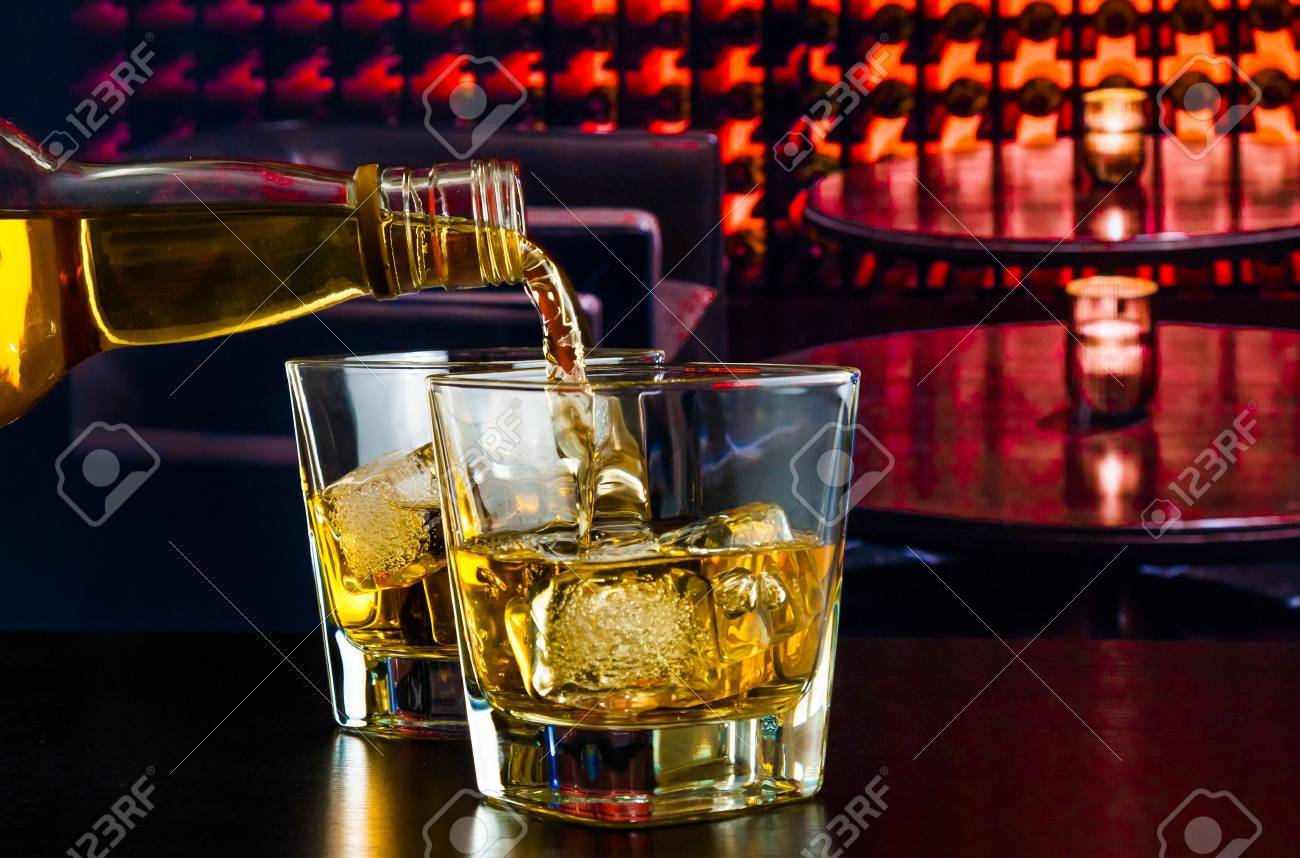 barman pouring whiskey in a lounge bar on wood table - 29463486