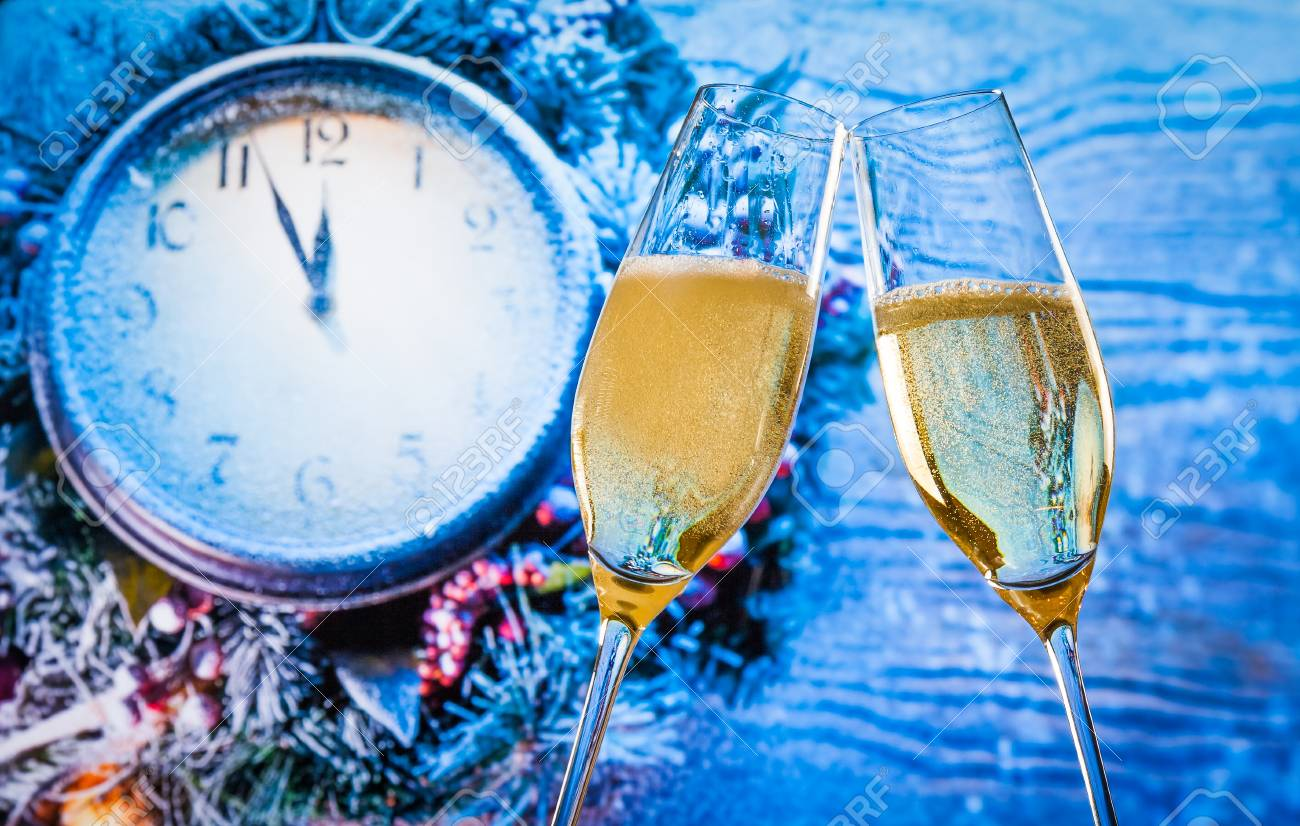 New Year or Christmas at midnight with champagne flutes with gold bubbles make cheers on blue light and clock background - 31207158