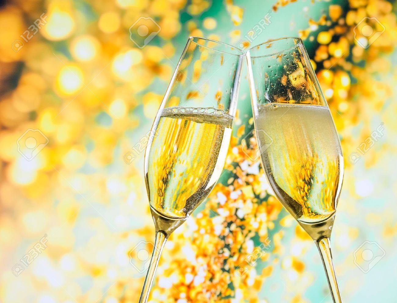 a pair of champagne flutes with golden bubbles make cheers on