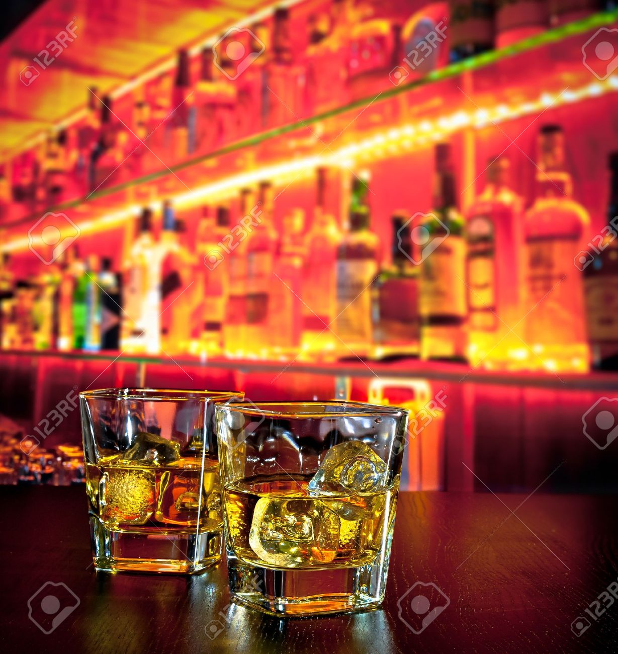 glasses of whiskey with ice on bar table near whiskey bottle on warm atmosphere lounge bar concept - 31406036