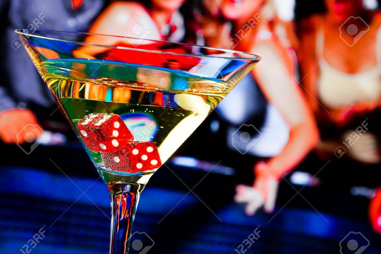 red dice in the cocktail glass in front of gambling table, casino series - 32455745