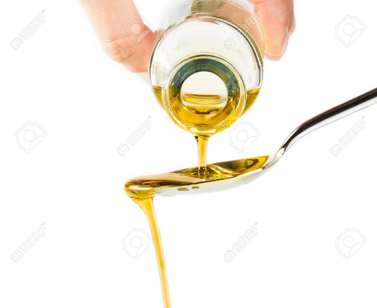 bottle of extra virgin olive oil pouring over a spoon isolated on white background with a space for text - 32853858