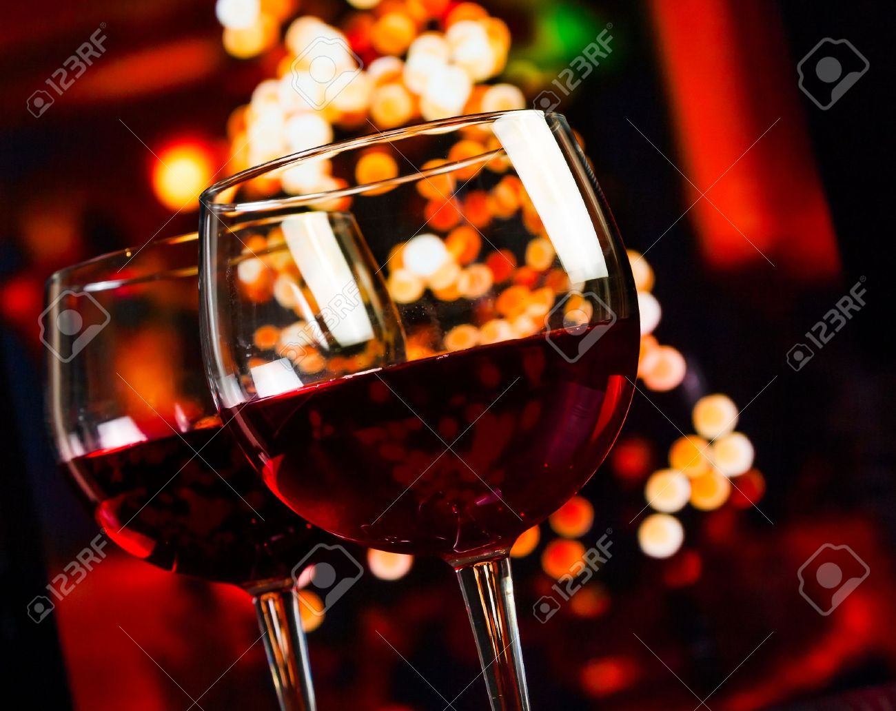 two red wine glass against christmas lights decoration background, christmas atmosphere - 33524423