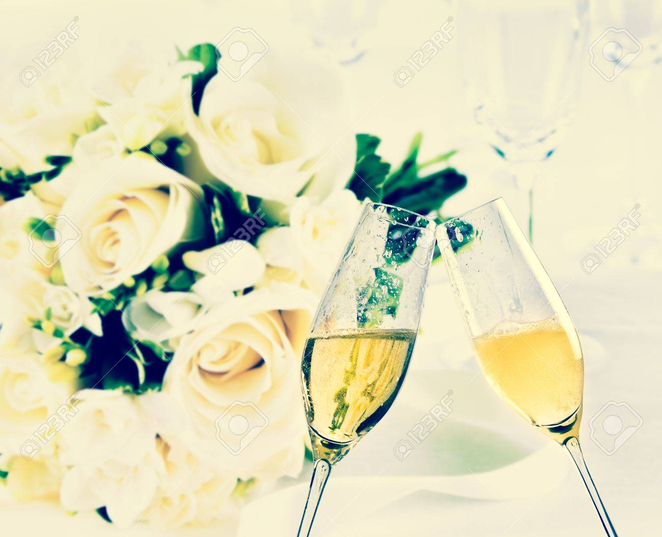 champagne flutes with golden bubbles make cheers on wedding flowers