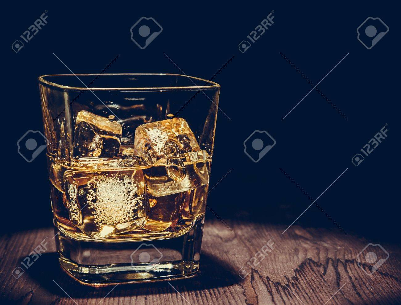 glass of whiskey with ice cubes on wood table, warm atmosphere, time of relax with whisky with space for text - 46673642