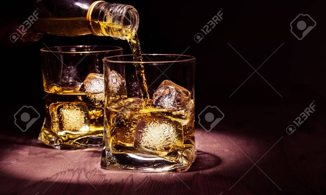 barman pouring whiskey in the glasses on wood table, warm atmosphere, old style, time of relax with whisky with space for text - 46799915