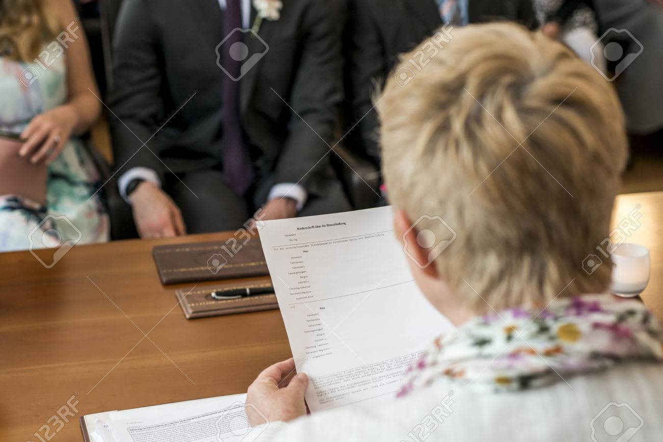 marriage registrar holding german wedding register reading bride