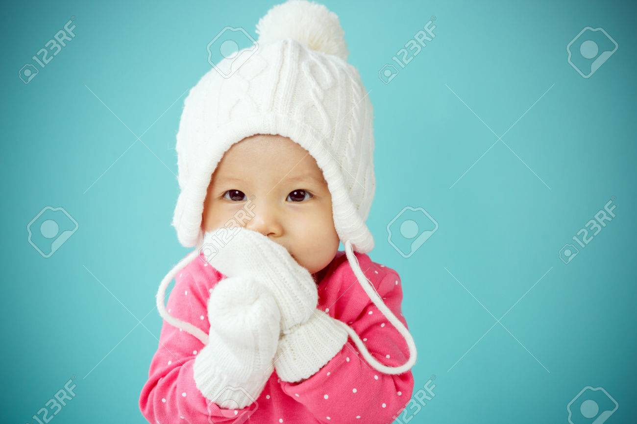 9693b649f Baby With White Poodle Hat And Knitted Mittens Stock Photo