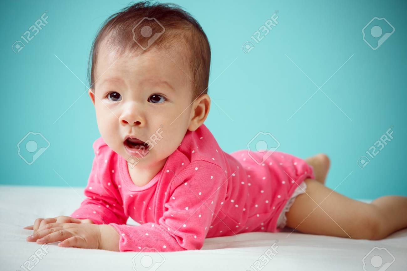 431753700 Cute Asian Baby Girl Lying On Stomach On Bed