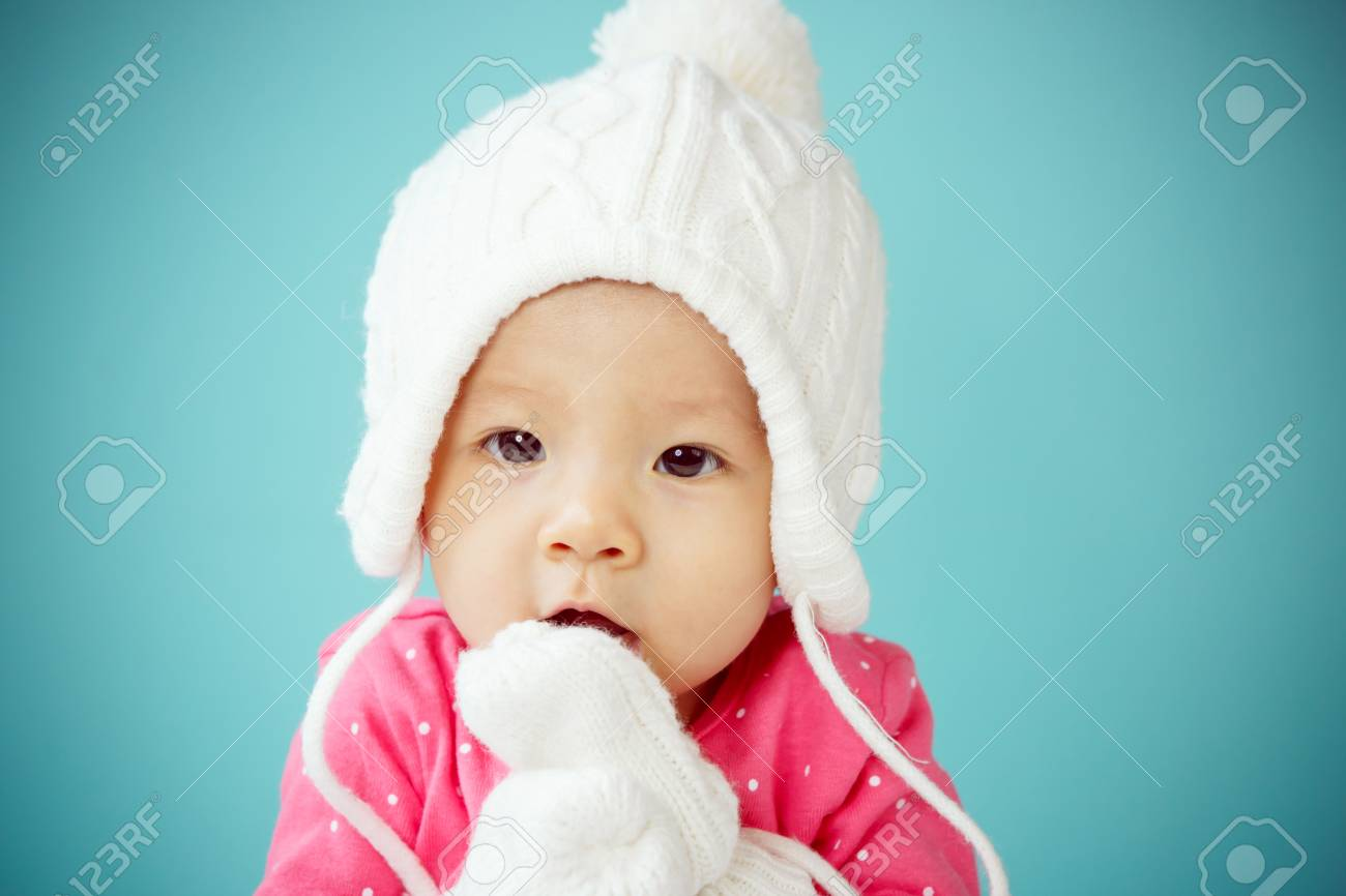 Little baby in knit winter clothing closing face with knitted beanie Stock  Photo - 42742723 cfc0eb8168d