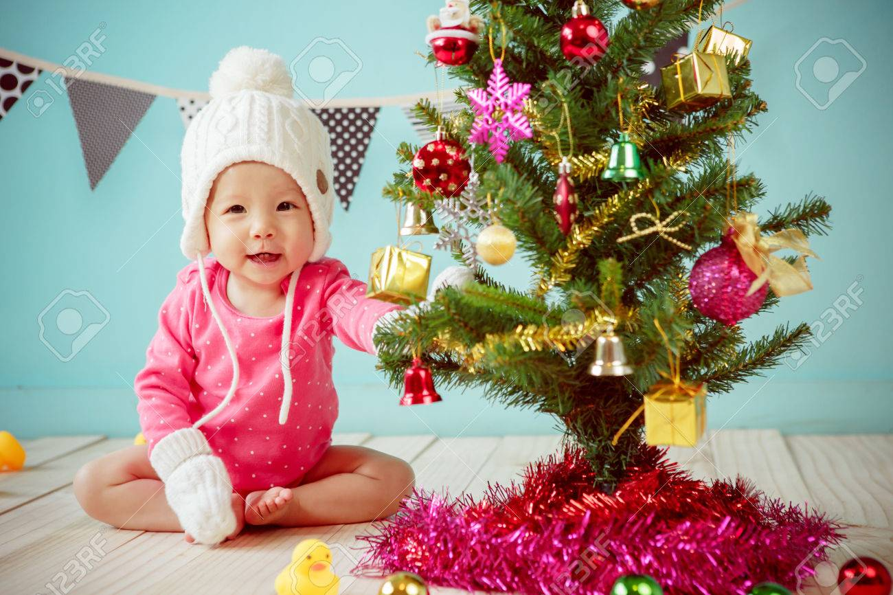 c7d2045b3 Newborn And Decorating Christmas Tree On Green Background Stock ...