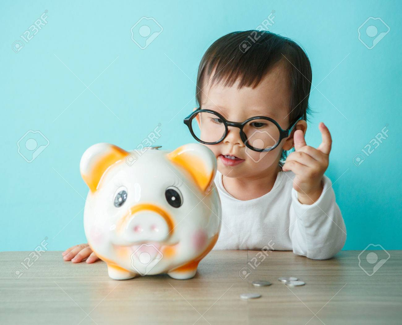Little Baby Moneybox Putting A Coin Into A Piggy Bank Kid Saving Stock Photo Picture And Royalty Free Image Image 67430290