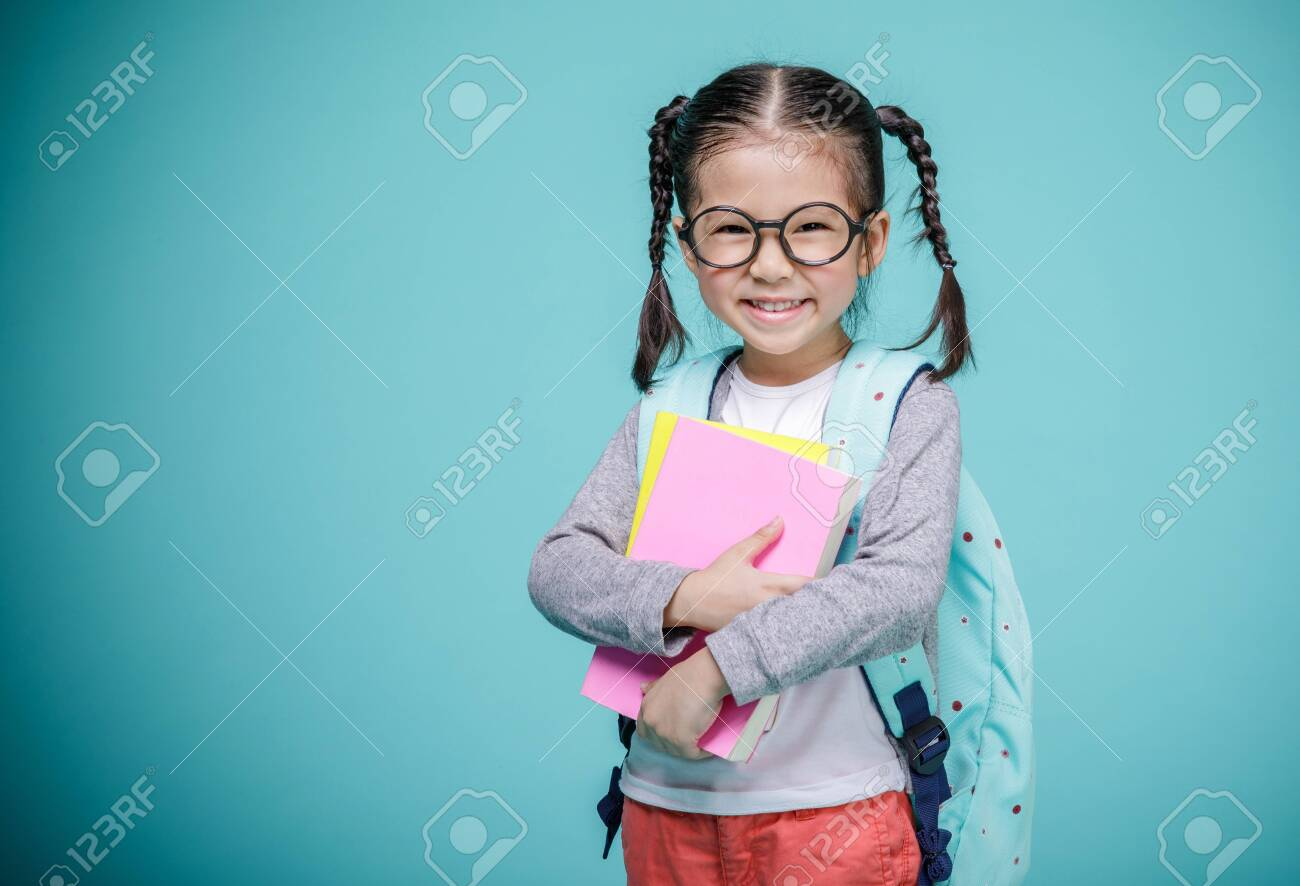 Beautiful smiling Asian little girl with glasses and hold a books with school bag is back to school, empty space in studio shot isolated on colorful blue background, Educational concept for school - 130726032