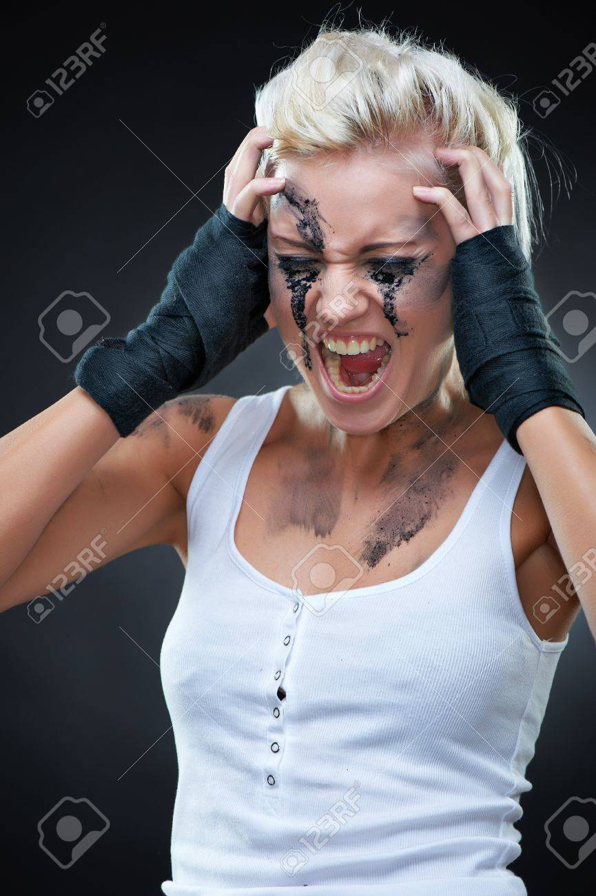 Emotional portrait of a beautiful screaming young punk woman with dirt on her face, studio shot Stock Photo - 9156624