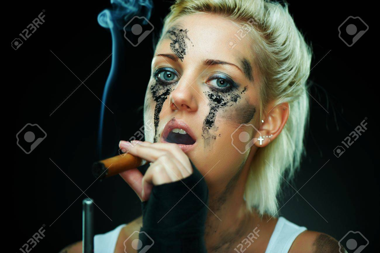 Closeup portrait of a beautiful young caucasian punk woman with dirty face and cigar in her mouth Stock Photo - 9156514