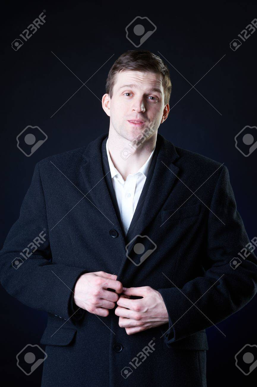 Studio dark portrait of a handsome stylish young man in coat Stock Photo - 9425680