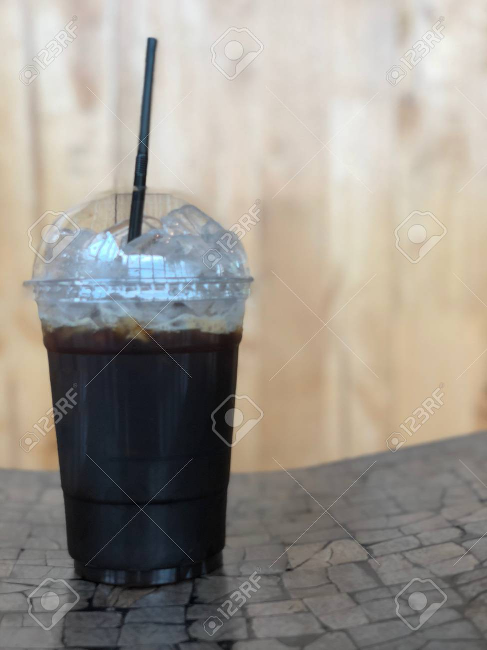 Iced black coffee or iced Americano with straw on wood table - 97967557