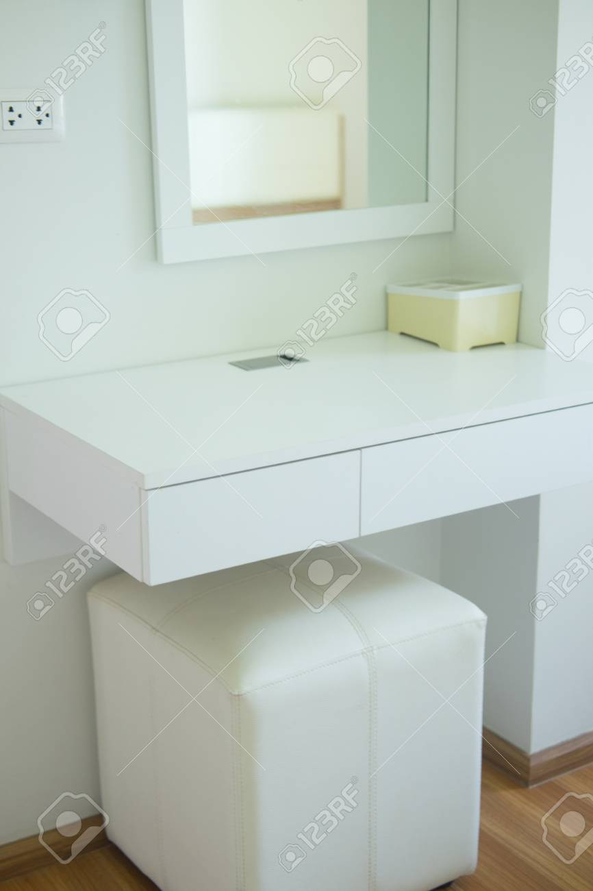 Small boudoir dressing table with small mirror in bedroom