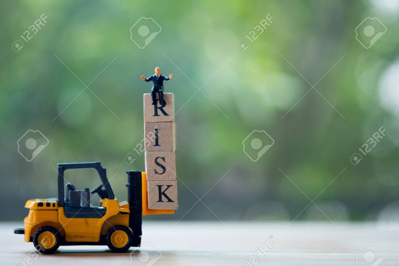 Miniature businessman sitting on top of unstable wooden blocks tower with alphabets combine word RISK. Risk assessment for business or investment - 118953654