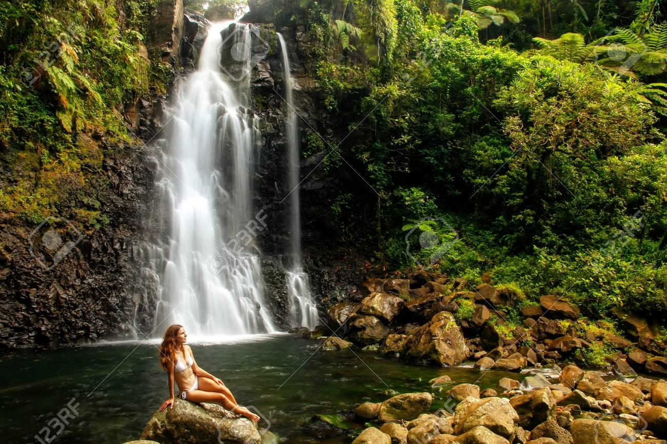 Young Woman In Bikini Sitting By Middle Tavoro Waterfalls In