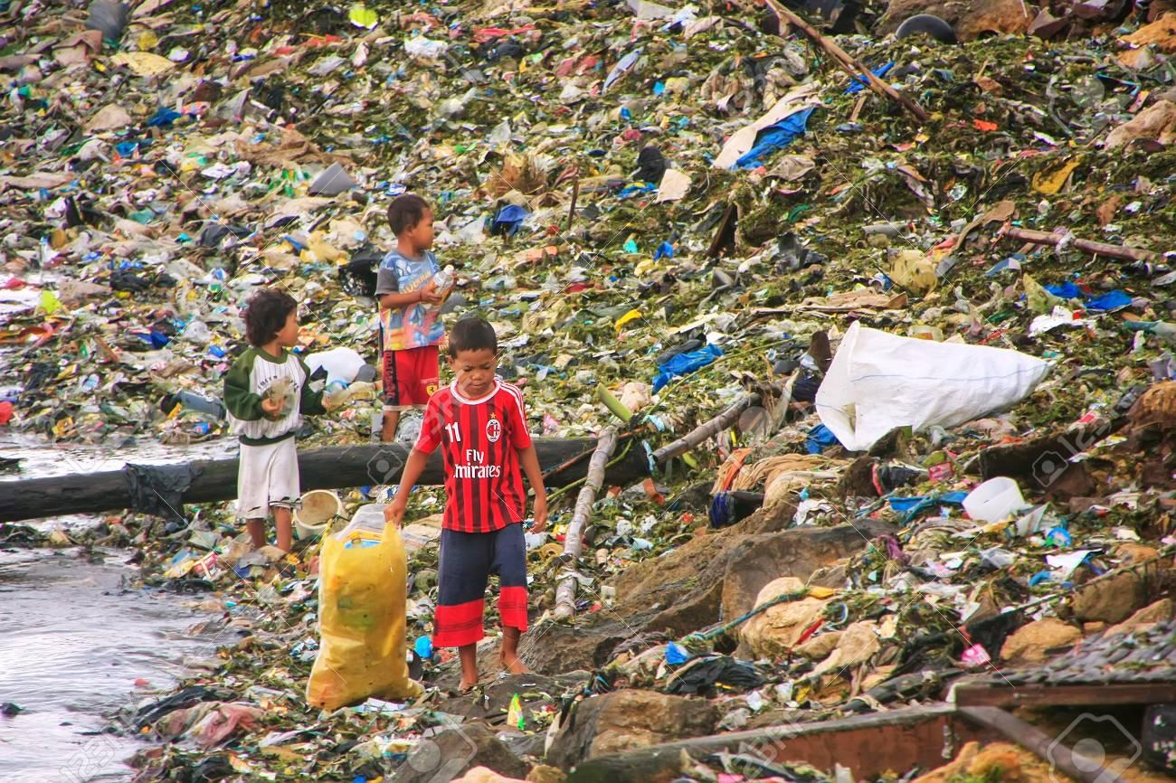 Bambini locali che attraversano i rifiuti sulla costa del mare nella città  di Labuan Bajo, Isola di Flores, Indonesia. L\'economia locale della città  ...