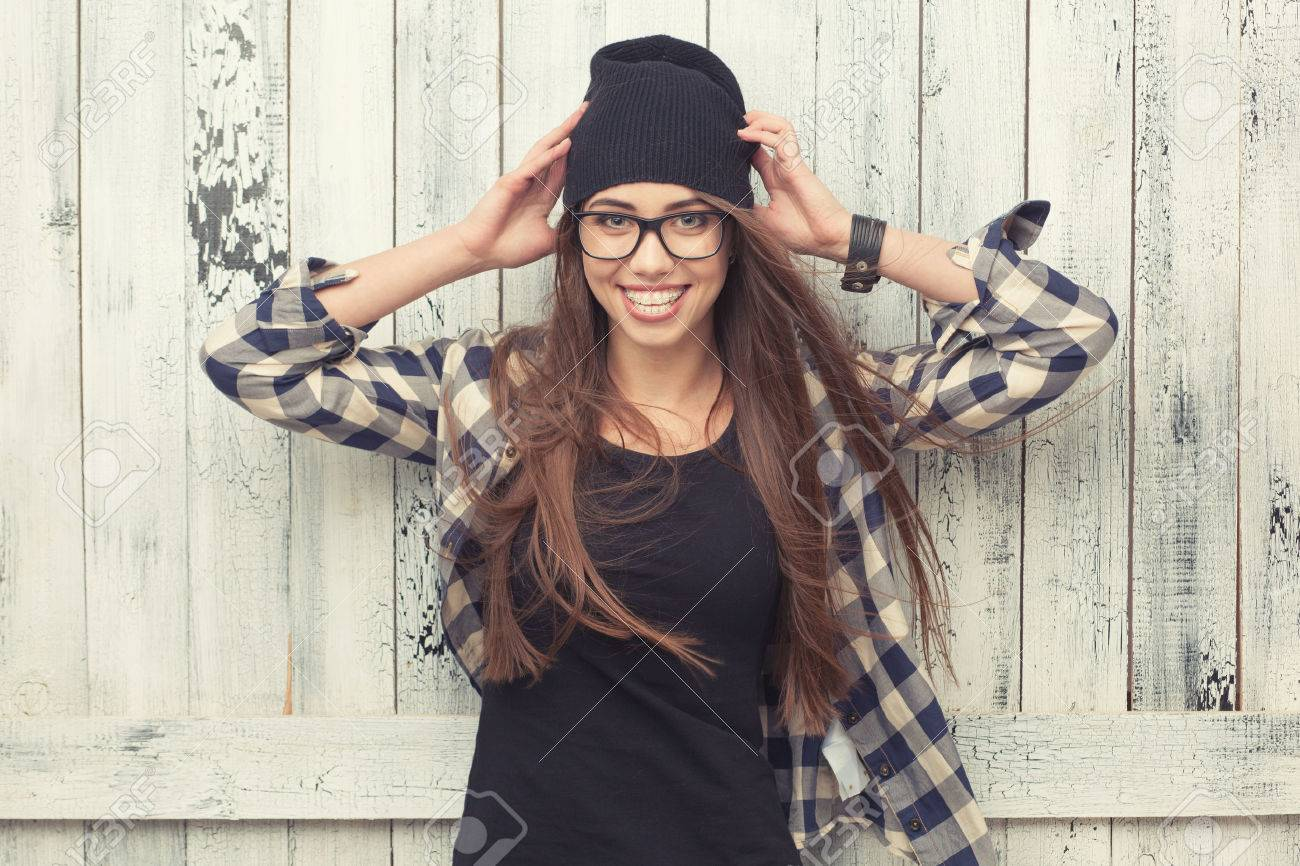 Smiling hipster girl in glasses and black beanie on the wooden background  Stock Photo - 39040999 e0c117b8a11