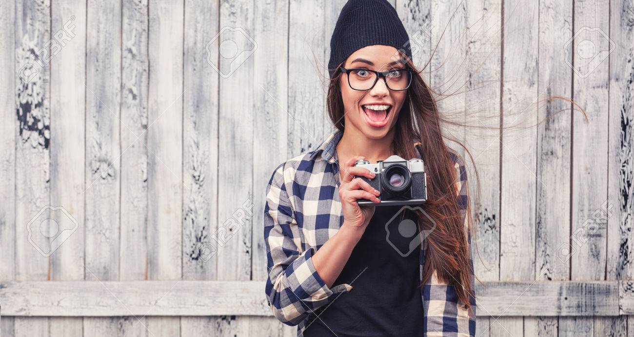 8aa3635d9ce Hipster girl in glasses and black beanie with vintage camera on the wooden  background Stock Photo