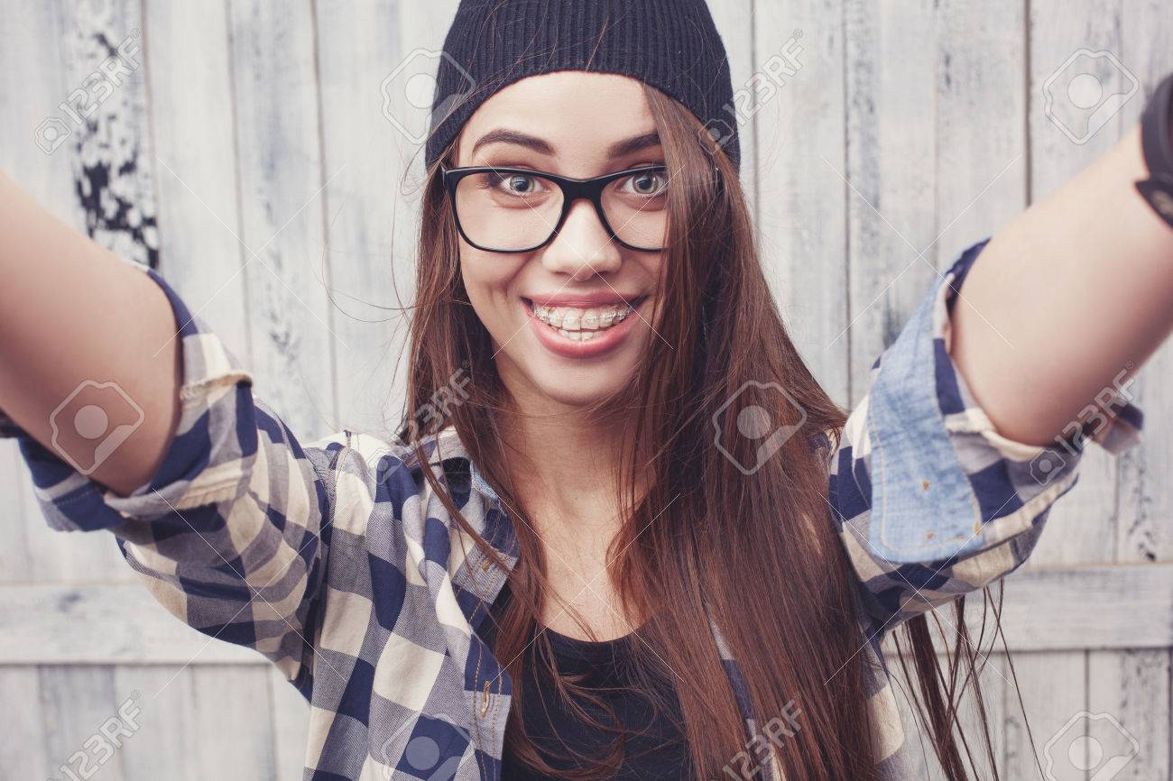 67444279534 Hipster girl in glasses and black beanie on the wooden background Stock  Photo - 40011017