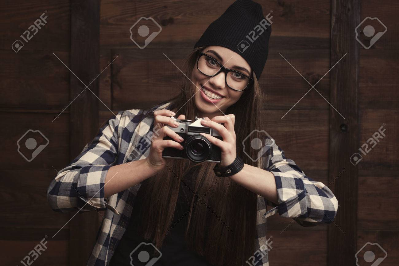 46039ad600a Hipster girl in glasses and black beanie with vintage camera on the wooden  Stock Photo -