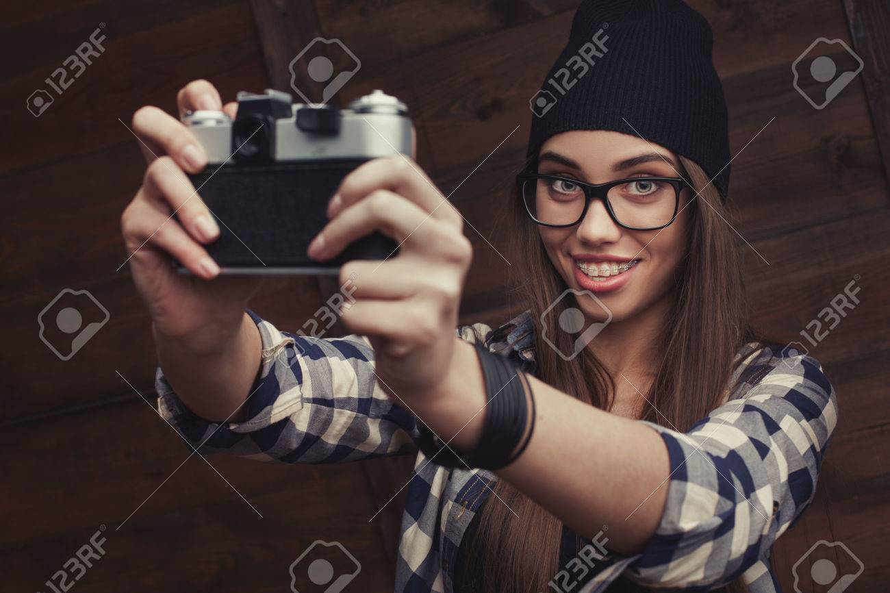 86c8042ca8d Hipster girl in glasses and black beanie with vintage camera making a  selfie shot on the