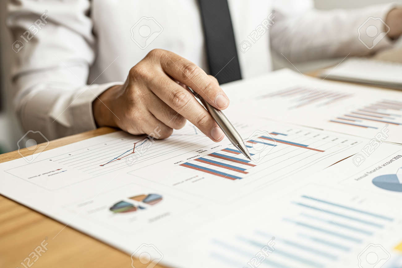 A close-up of a financial businessman holding a pen and pointing at the information sheet on his desk, reading the company's financials to make a financial plan. Financial concept. - 168079879