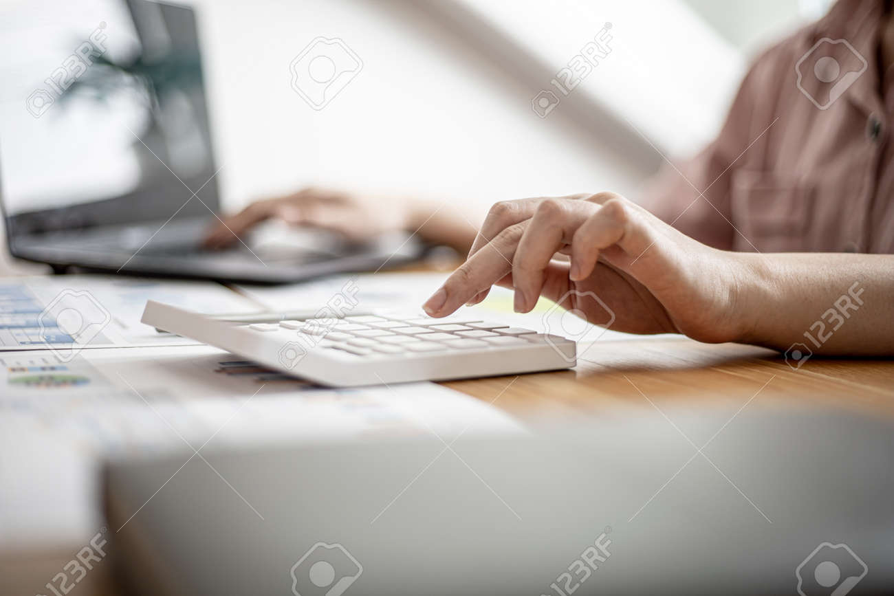Businesswoman is using a calculator to check the numbers on a company financial document during a meeting with shareholders, corporate finance documents showing a bar graph format. Financial concept. - 168447381