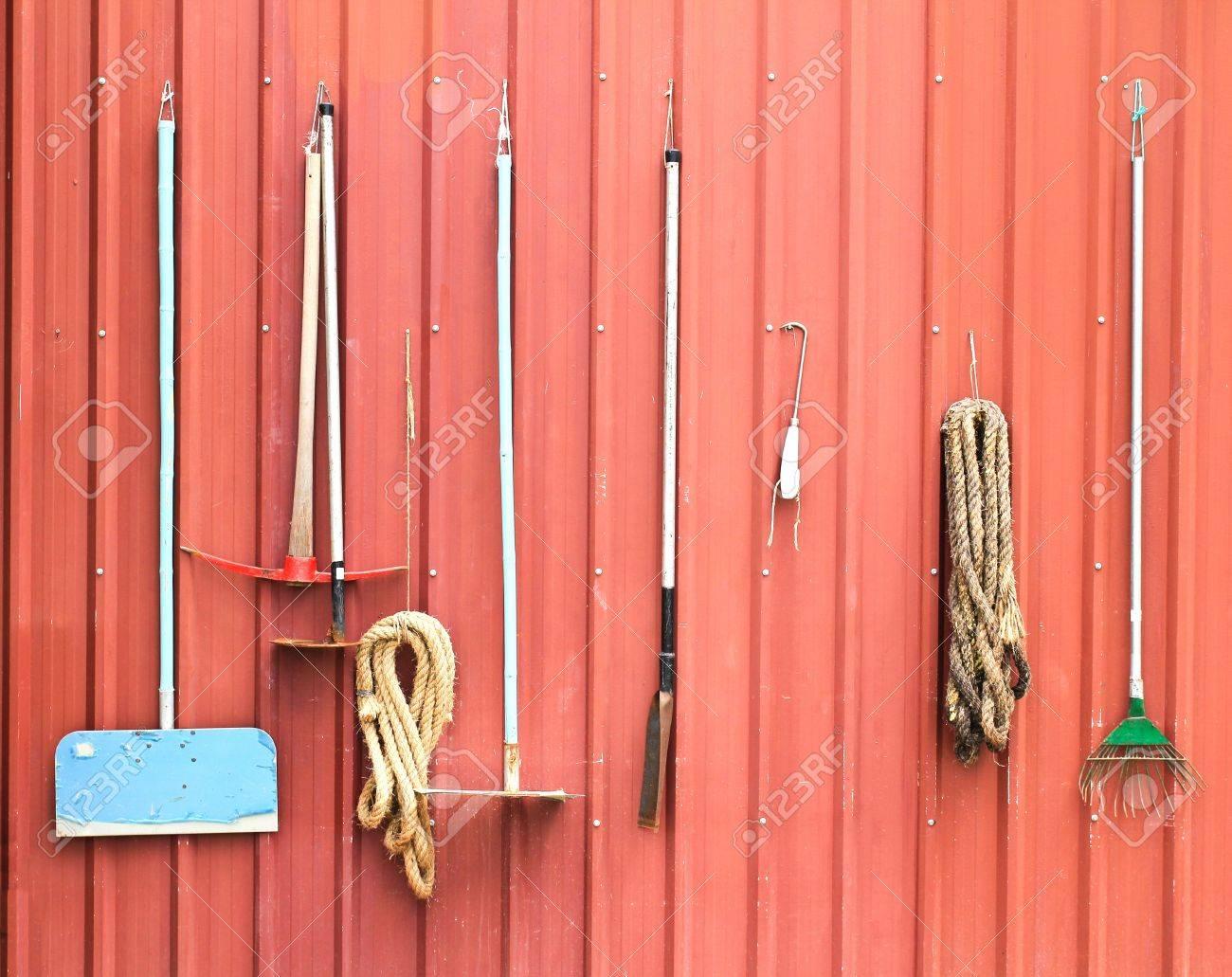 Farm tools hang on red barn wall Stock Photo - 21796861
