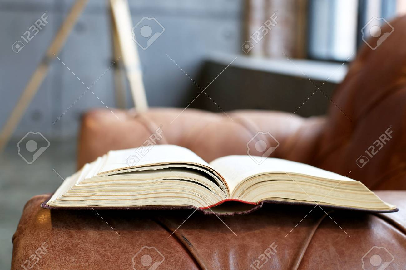 Thick Book In Hardcover On A Leather Sofa
